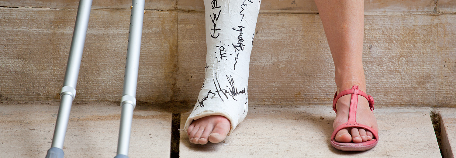 A person with crutches and a signed plaster cast on their leg
